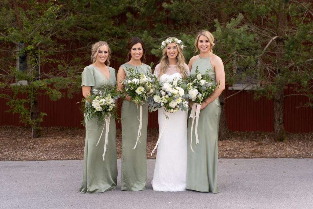 Bride in white and her bridesmaids in green dresses holding their flower bouquets