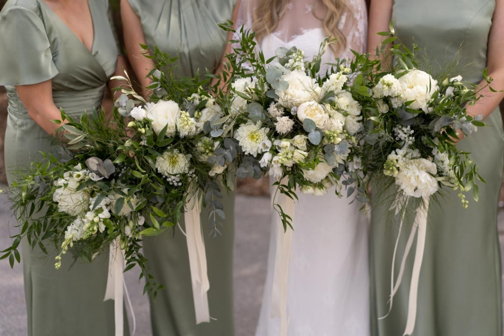 Bride and her Bridesmaids holding their white flower bouquets