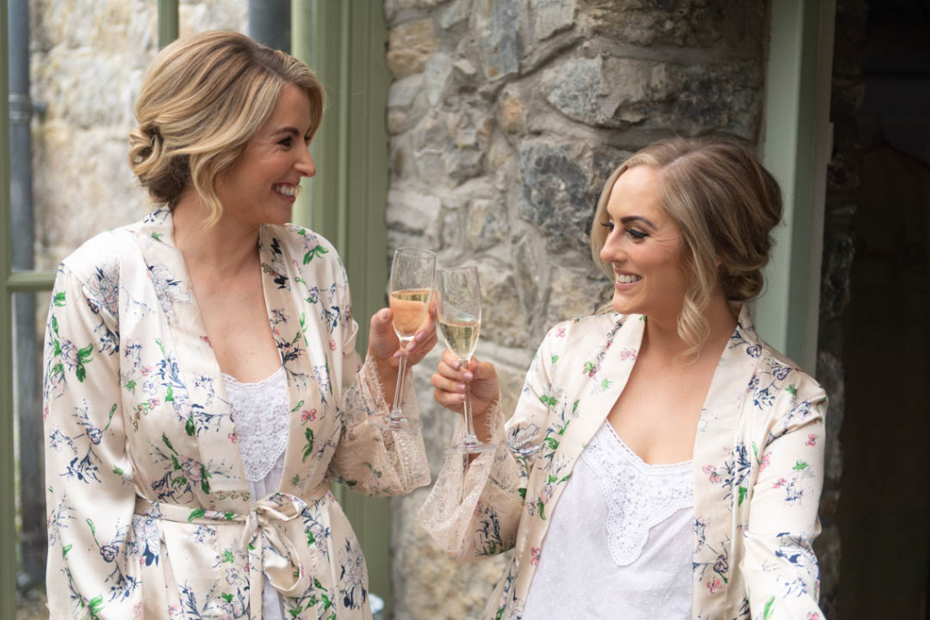 Bridesmaids in their bridal robes clinking champagne glasses