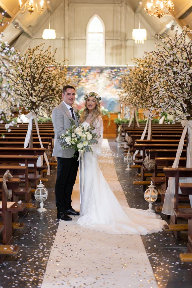 Bride and groom standing and surrounded by blossom trees in the Tin Chapel in Mount Druid