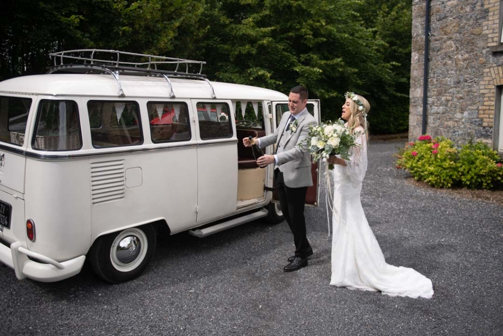 Bride and groom popping champagne beside their white volkswagen wedding van