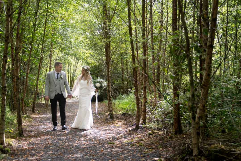 Bride and Groom holding hands walking through the forest at Mound Druid