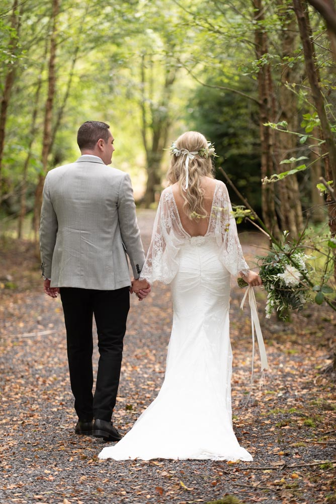 Bride and groom walking through the forest at Mount Druid