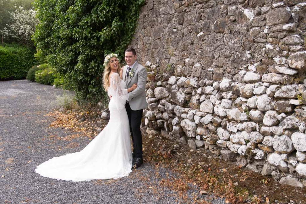 Bride and Groom standing by a stone wall on the grounds of Mount Druid
