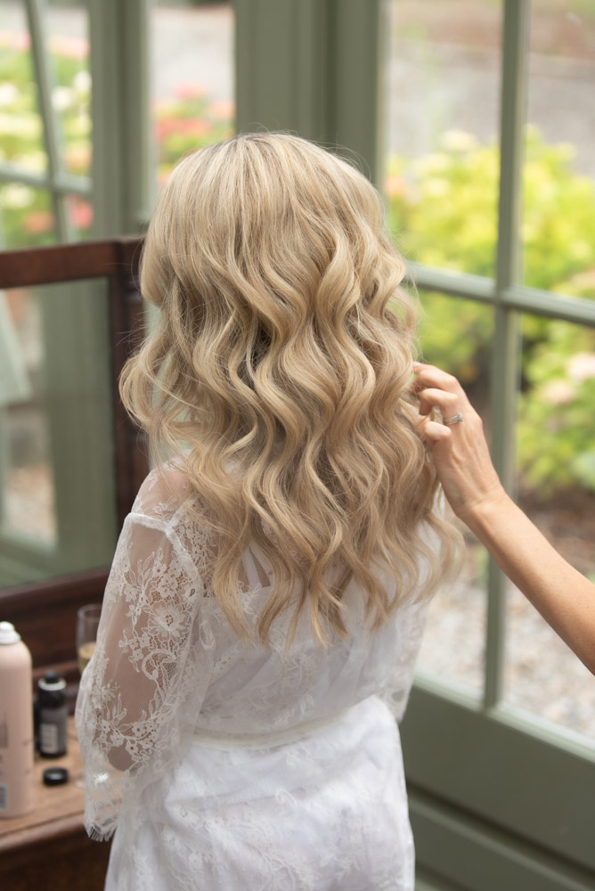 The back of the Brides blonde wavy hairstyle for her wedding