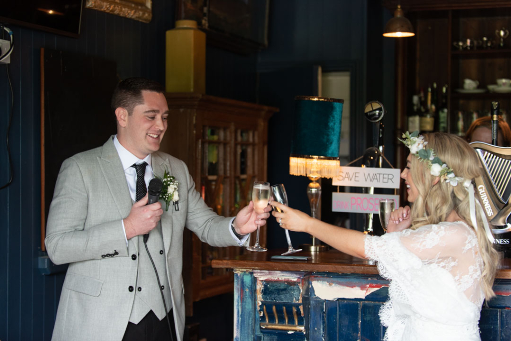 Bride and Groom clinking champagne glasses at their Mount Druid wedding