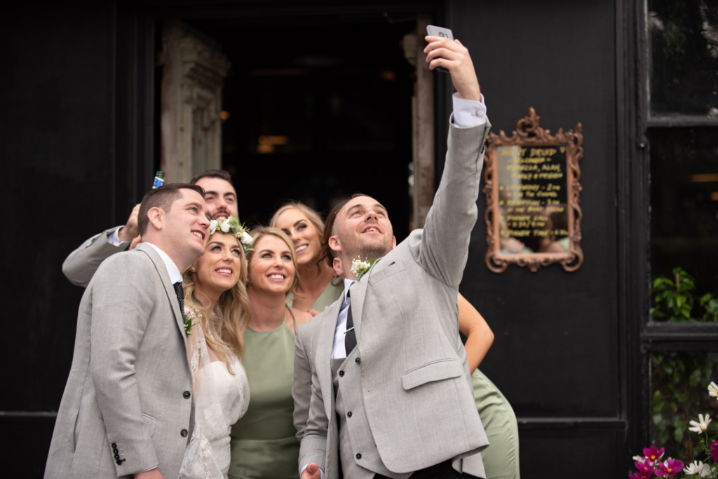 Bride and Groom and their bridal party taking a selfie photo together