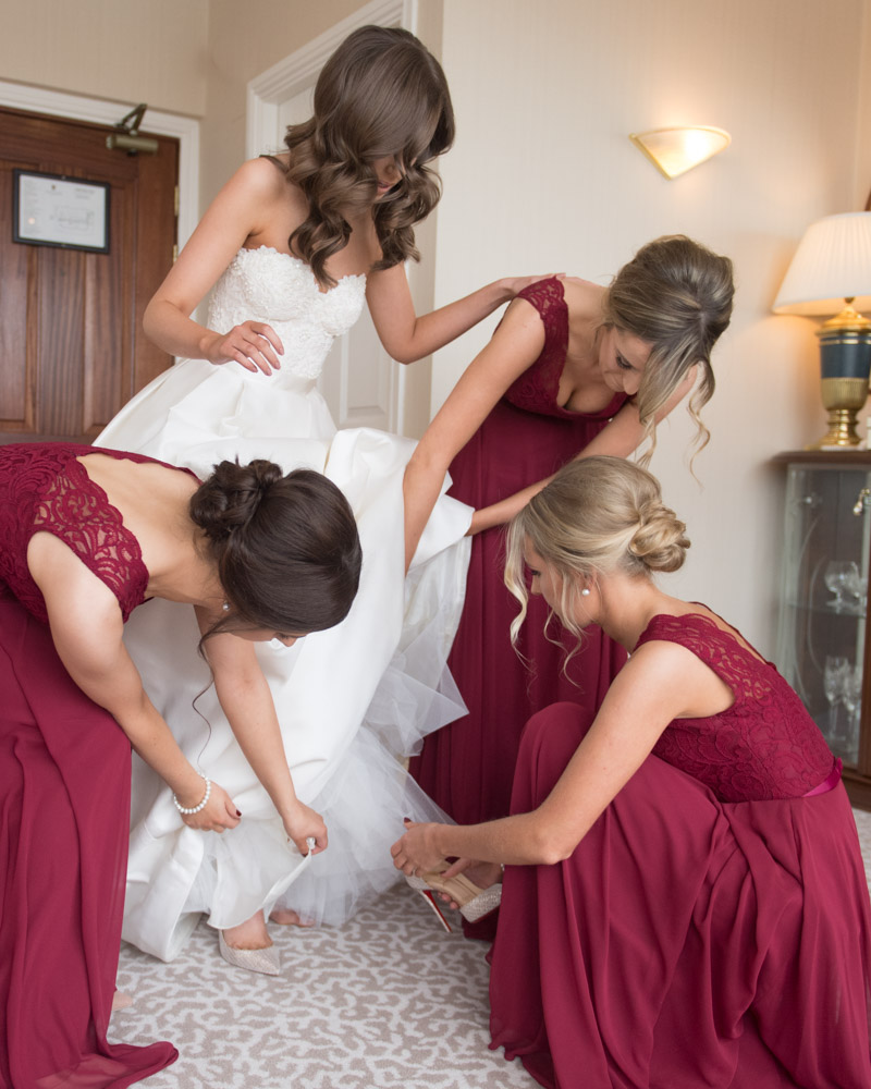 Bridesmaids putting the Brides shoes on for the Bride