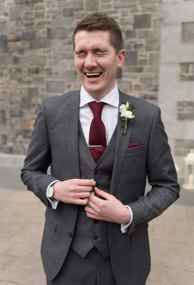 Groom laughing outside the Church