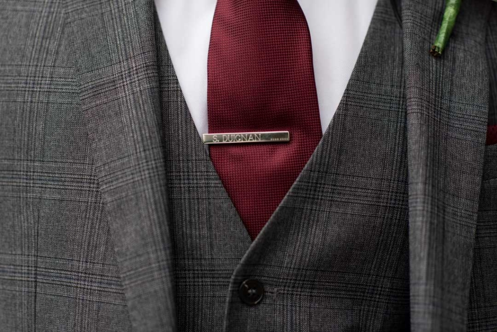 Grooms suit, tie and tie pin with the grooms name engraved on the tie pin
