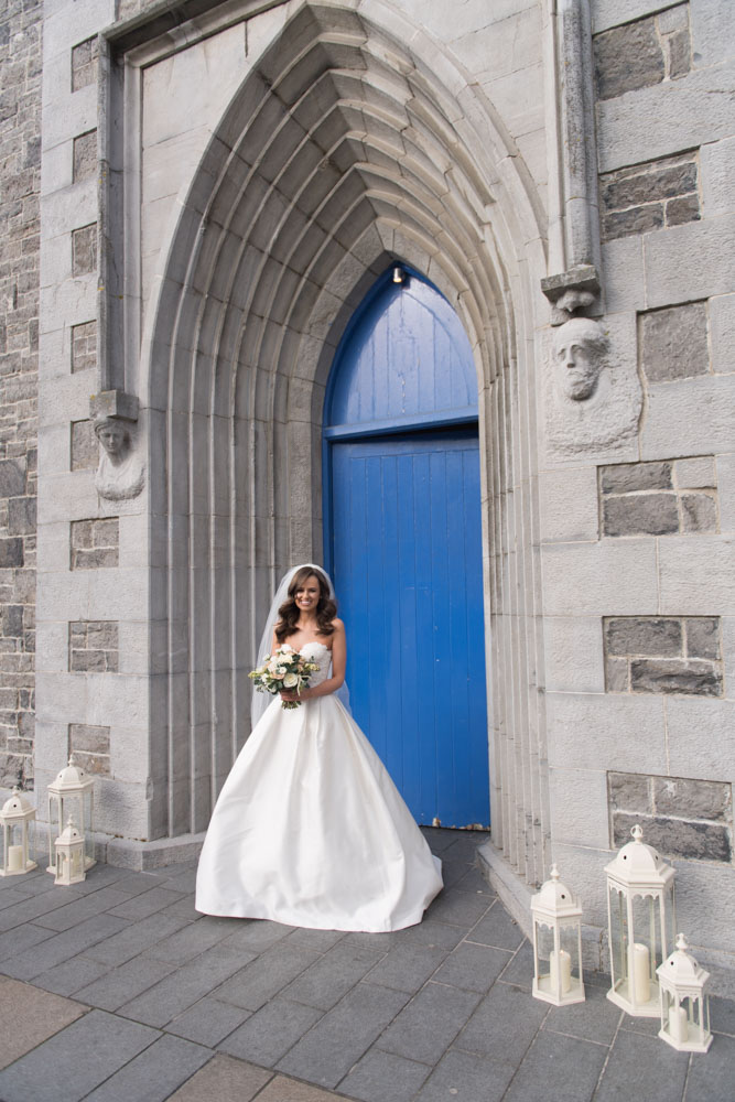 Bride holding her flower bouquet standing in front of the Blue church door