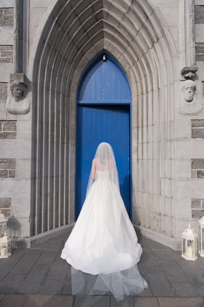 The back of the Bride and her dress facing the Church door
