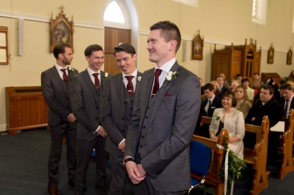 Groom looking nervous and groomsmen laughing at the top of the Church before Bride walks in