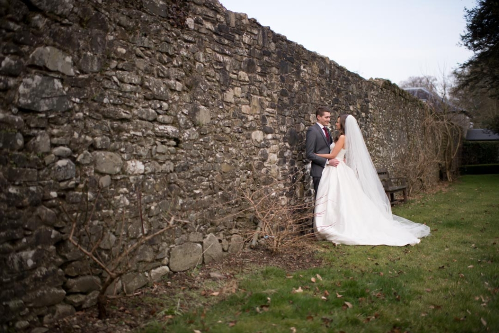 Bride and Groom standing by a stone wall at Tankardstown House