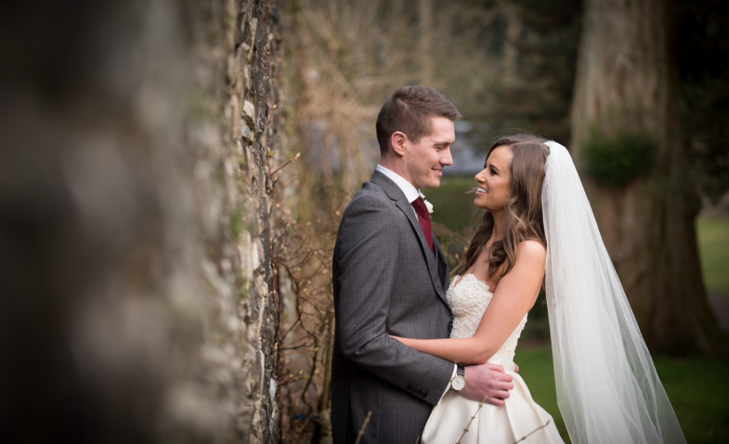 Bride and Groom standing and looking at each other by a stone wall at Tankardstown House