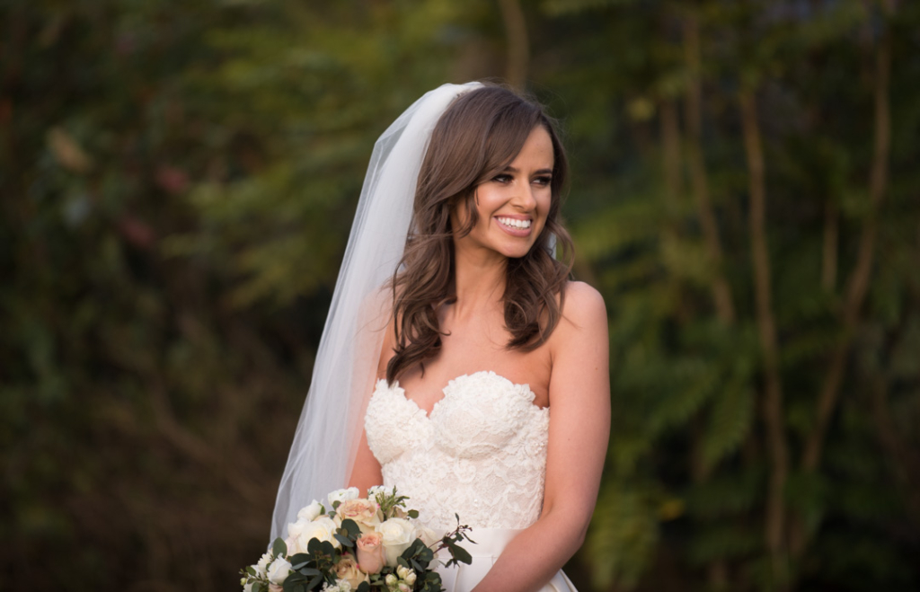 Bride wearing a veil and holding wedding flower bouquet in the gardens of Tankardstown House