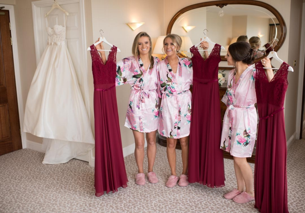 Bridesmaids in their wedding robes holding their bridesmaids dresses