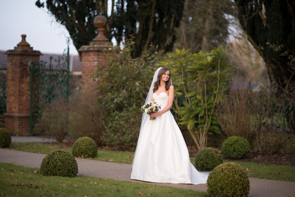 Bride standing and holding wedding flower bouquet in the gardens of Tankardstown House