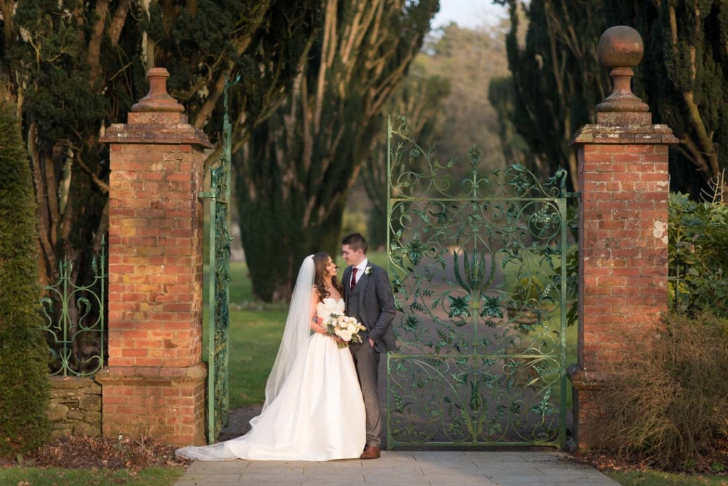 Bride and Groom standing together at the green gates at Tankardstown House