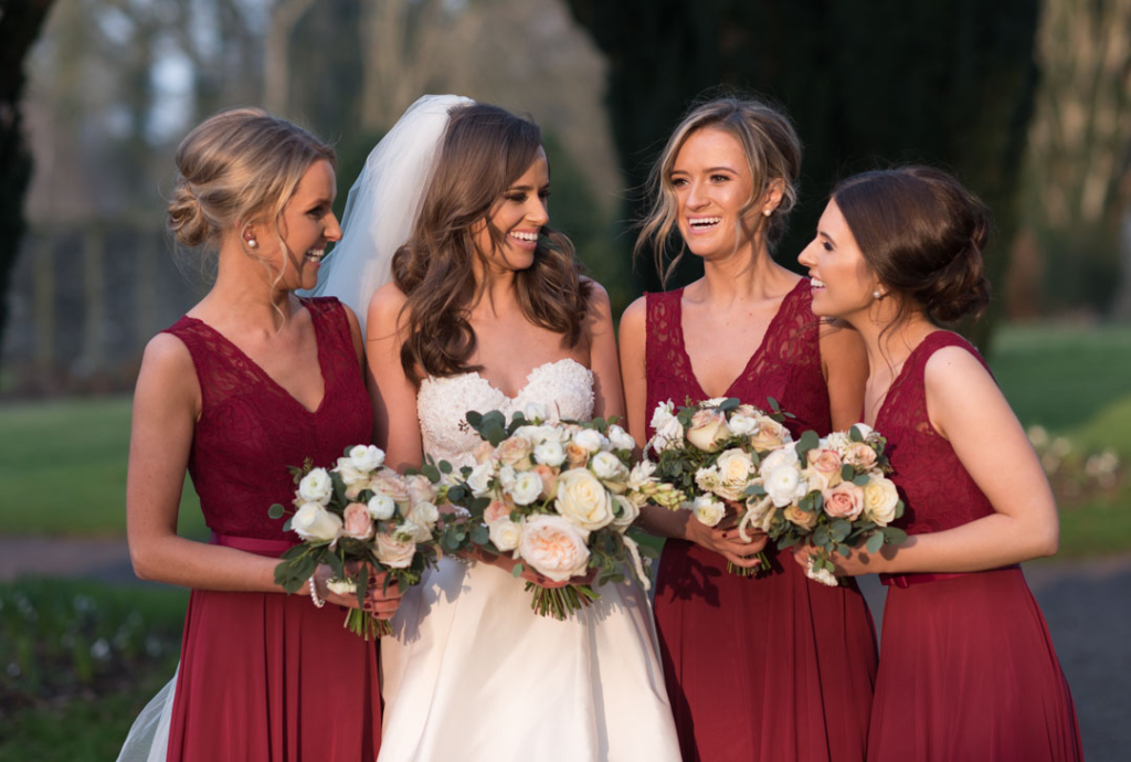 Bride and bridesmaids laughing together in the gardens at Tankardstown House