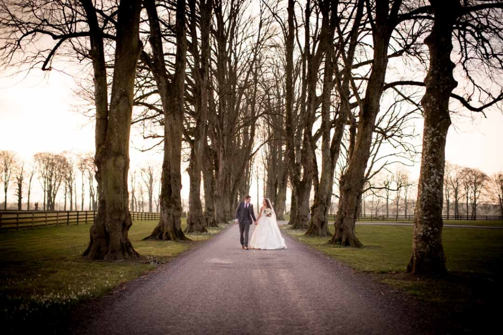 Bride and Groom holding hands while walking down the driveway at Tankardstown House