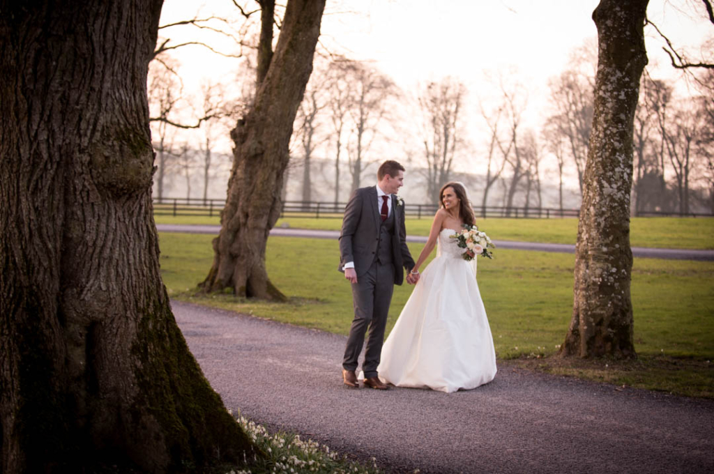 Bride and Groom smiling and looking at each other while walking down the driveway at Tankardstown House