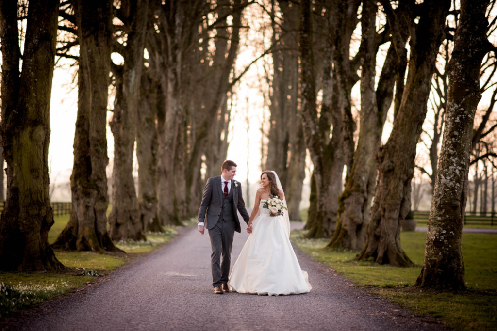 Bride and Groom walking down the driveway lined by trees at Tankardstown House