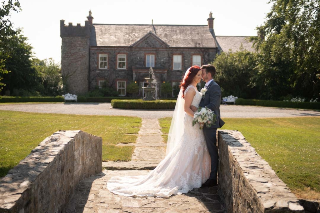 Bride and groom on bridge in front of Ballymagarvey House
