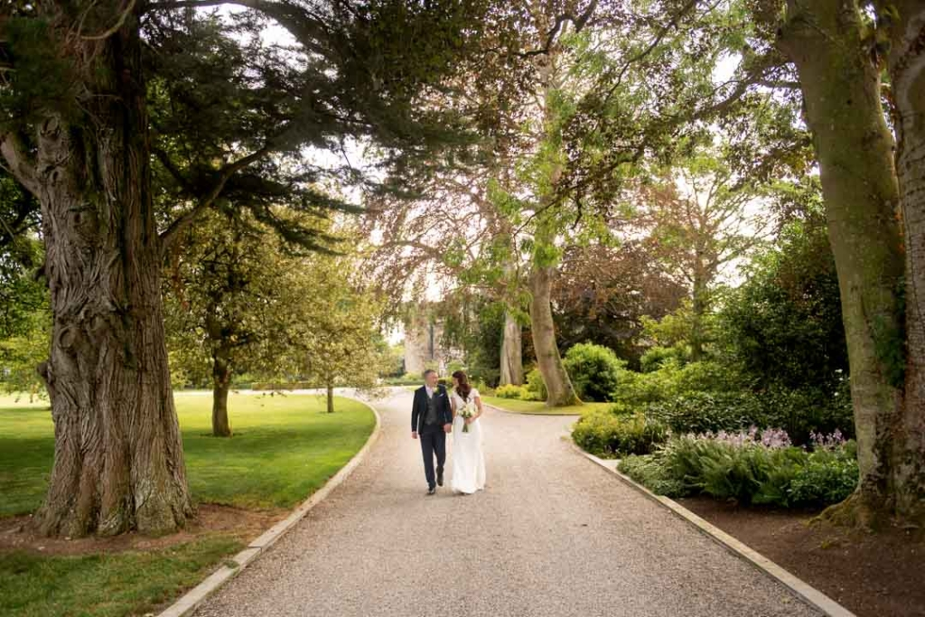 Bride and Groom walking down the driveway at Ballymagarvey Village surrounded by big trees