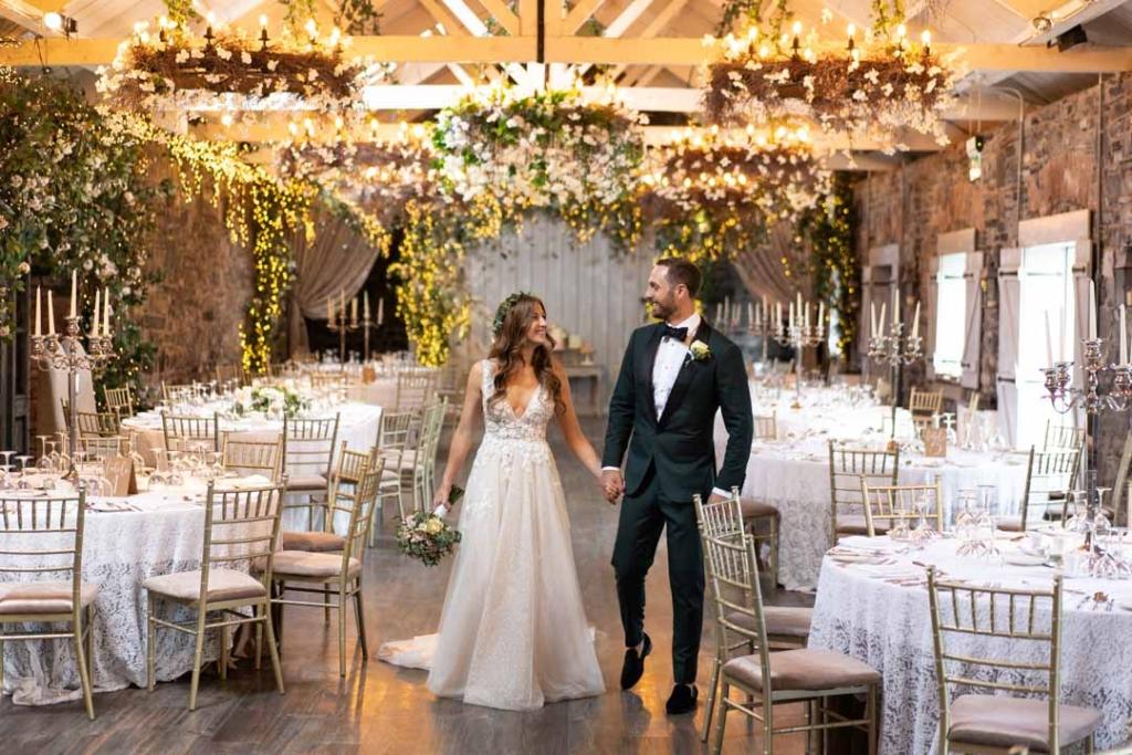 Bride and Groom walking through the wedding reception room at Ballymagarvey