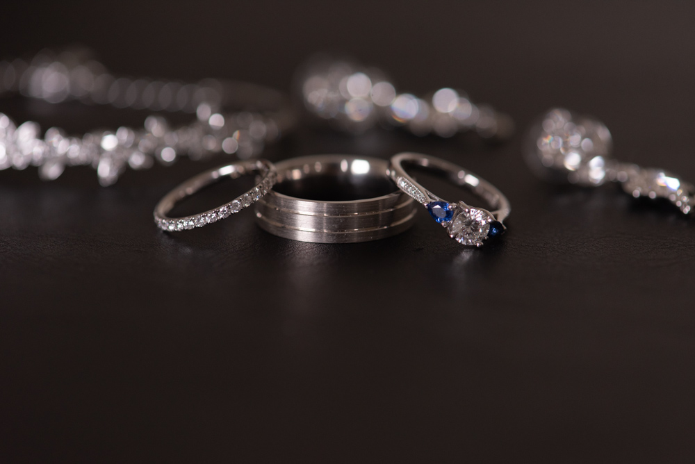 Diamond engagement ring with his and hers wedding bands on a table