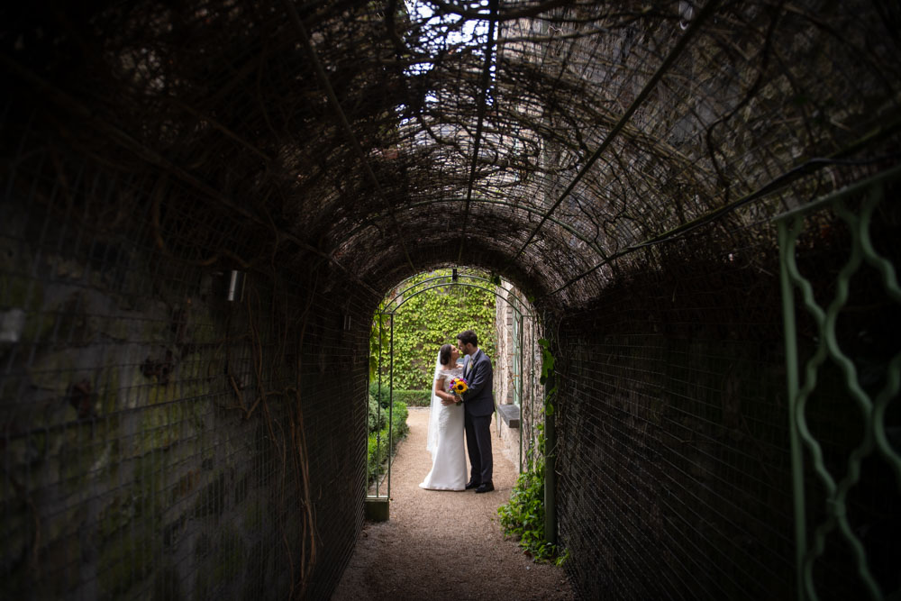 Bride and Groom kissing at the end of a garden tunnel