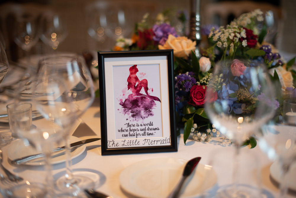 The disney themed table place names on each table in a photo frame