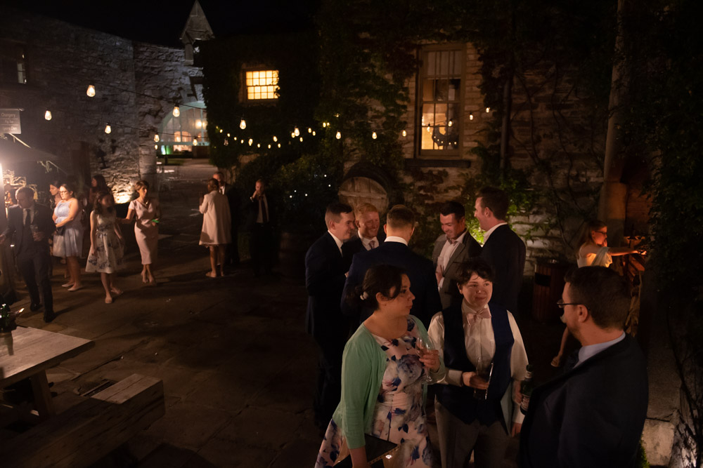 Guests out chatting in the courtyard of the Cliff at Lyons wedding venue