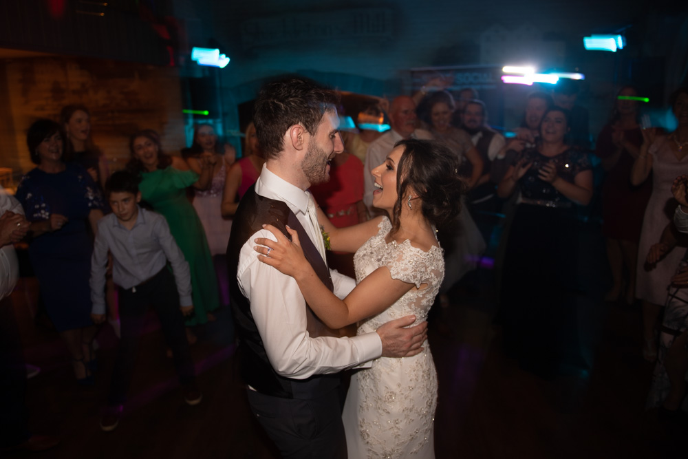 Bride and Groom singing and dancing with their guests surrounding them on the dance floor