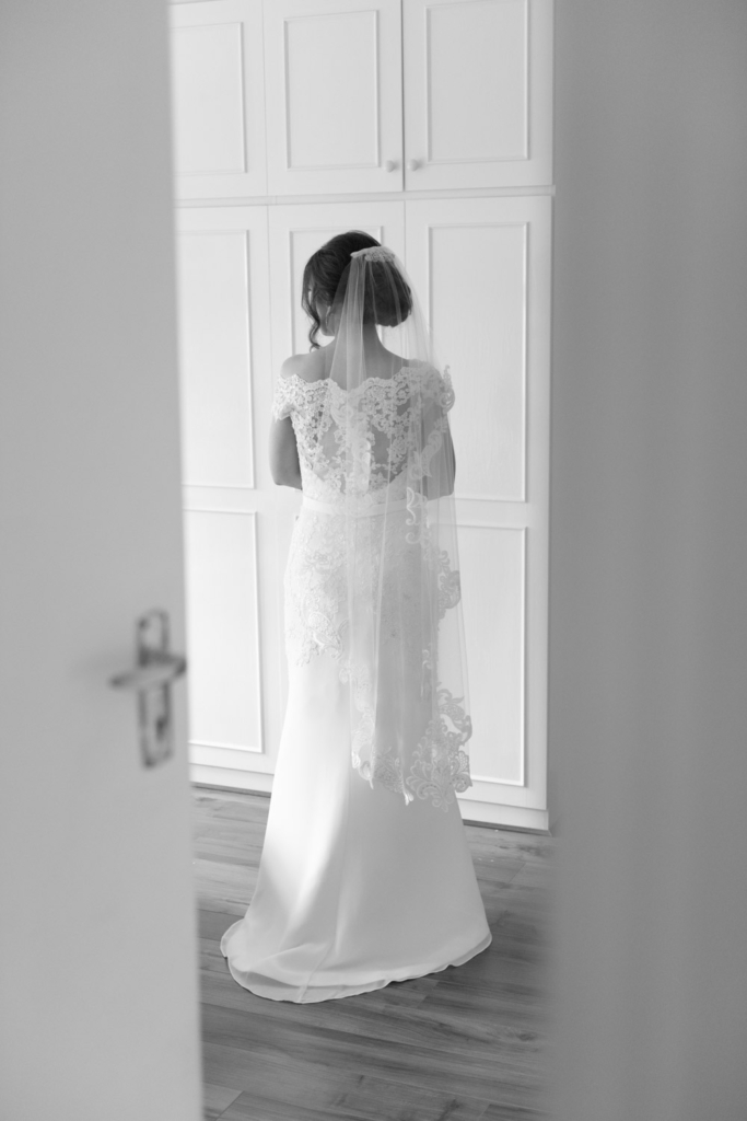 Bride in her white wedding dress and veil on the morning of her wedding in her bedroom