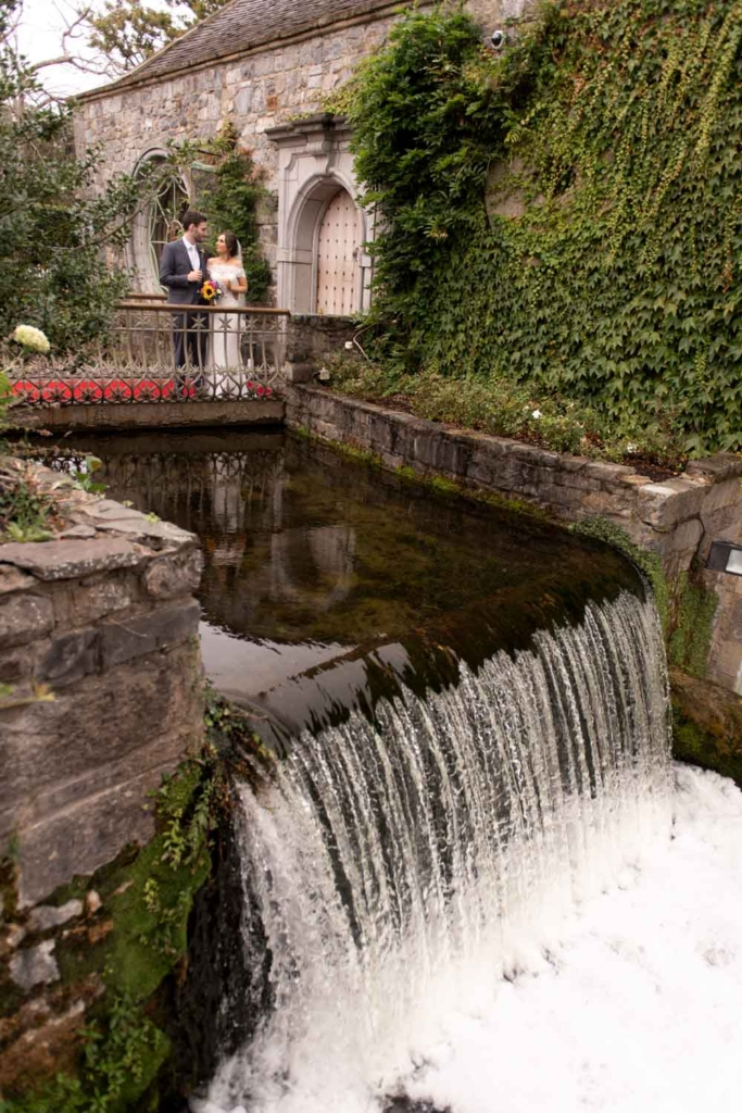 Bride and Groom standing over the waterfall at the entrance to the Cliff at Lyons in Kildare