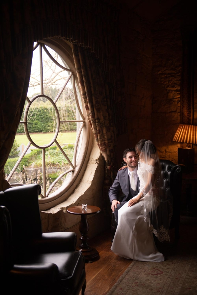 Bride and Groom sitting by the round window at the Cliff at Lyons wedding venue