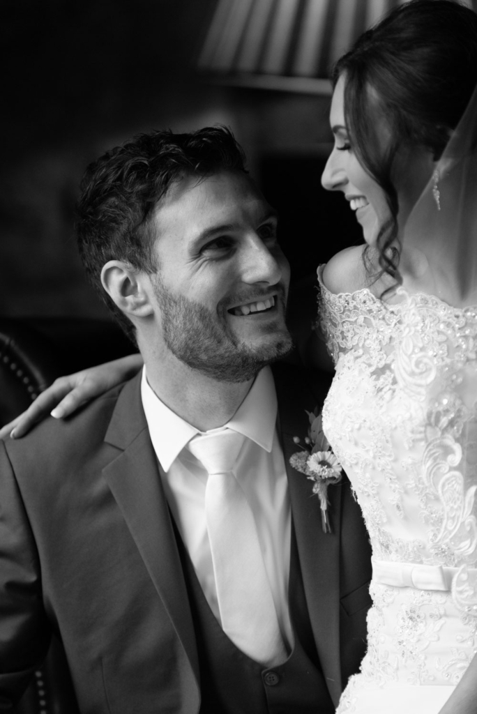 Bride sitting on the Grooms knee and smiling together