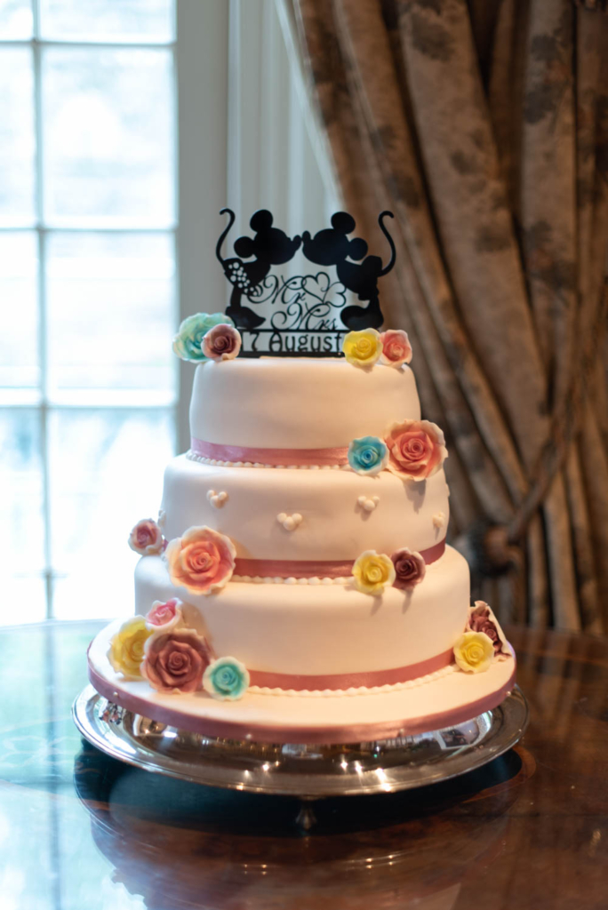 White wedding cake with colourful iced flowers and a minnie and micky mouse on top