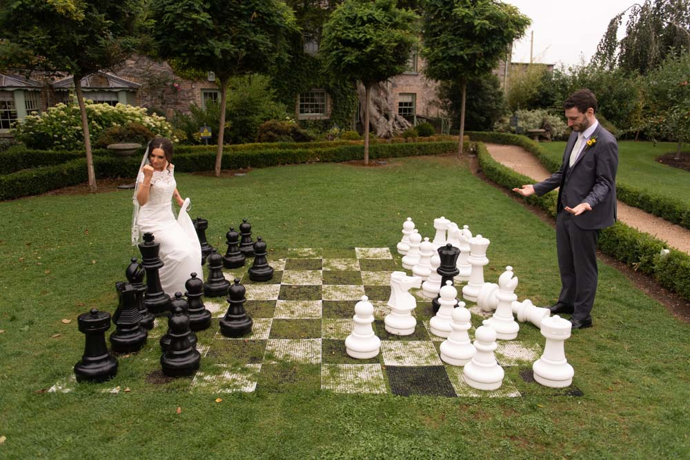 Bride and Groom playing jumbo chess on the lawn at the Cliff at Lyons