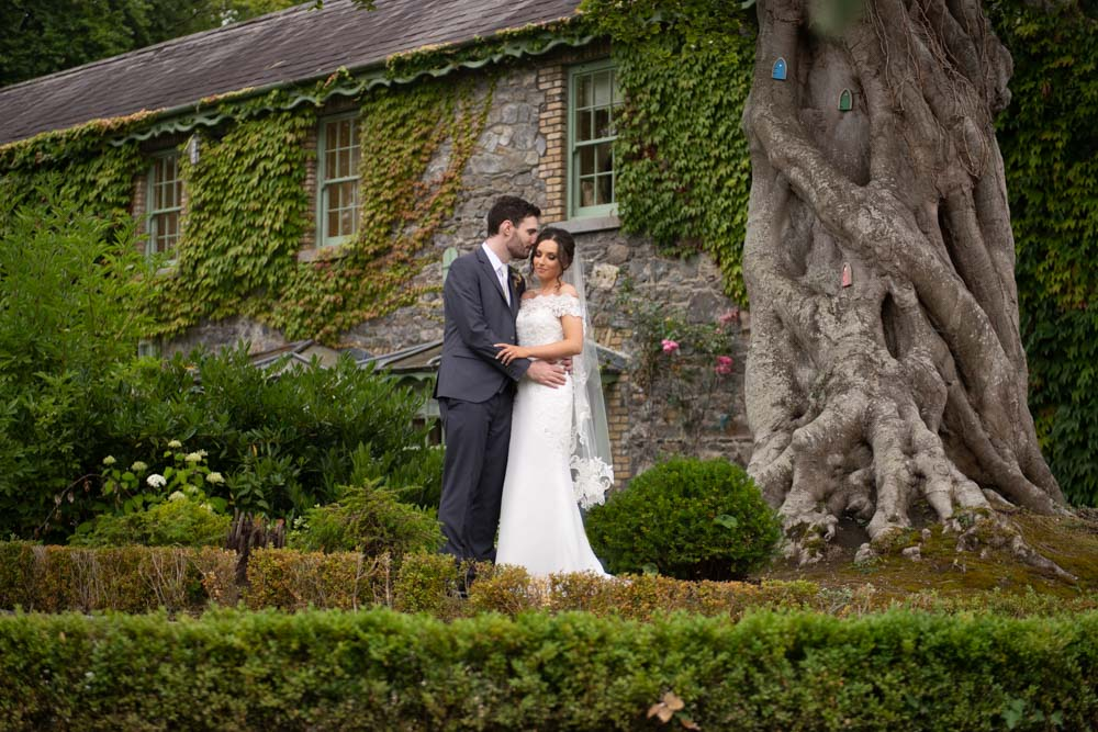 Bride and Groom getting their photo taken beside a fairy tree on the grounds of Cliff at Lyons wedding venue