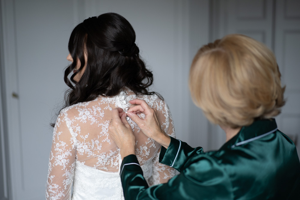 Mother of the Bride buttoning up the Brides wedding dress