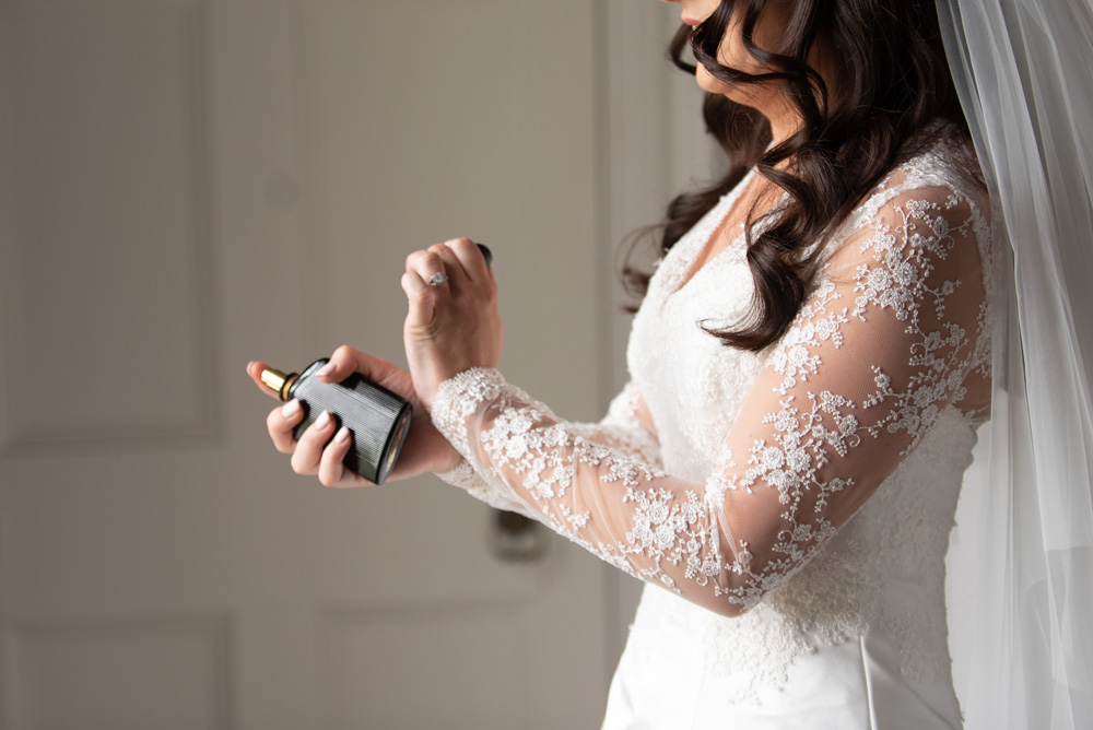 Bride putting on her perfume