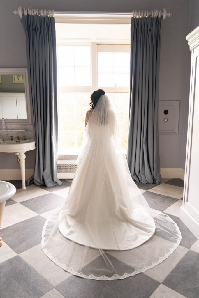 The Bride at the window in her wedding dress for her Ireland castle wedding