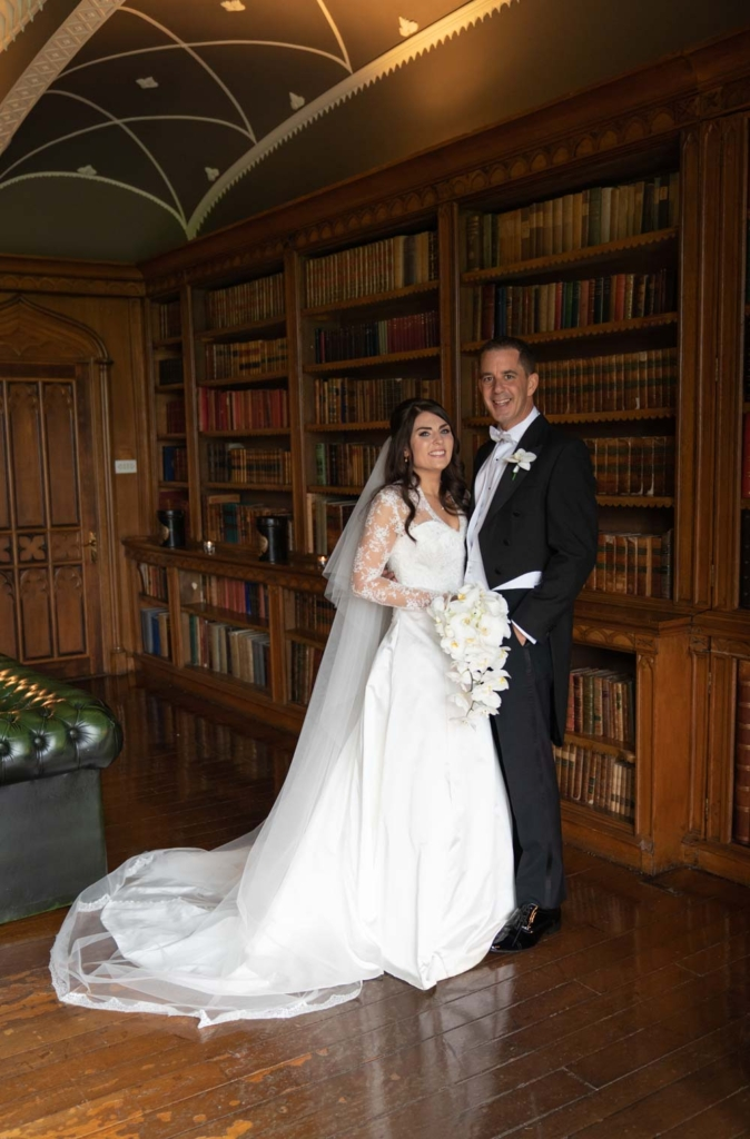 Bride and Groom standing in the library at Luttrellstwon Castle