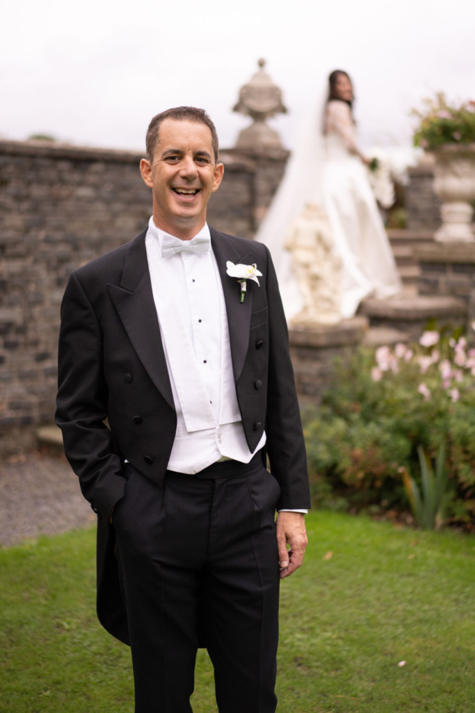 Groom smiling at camera with Bride in the background