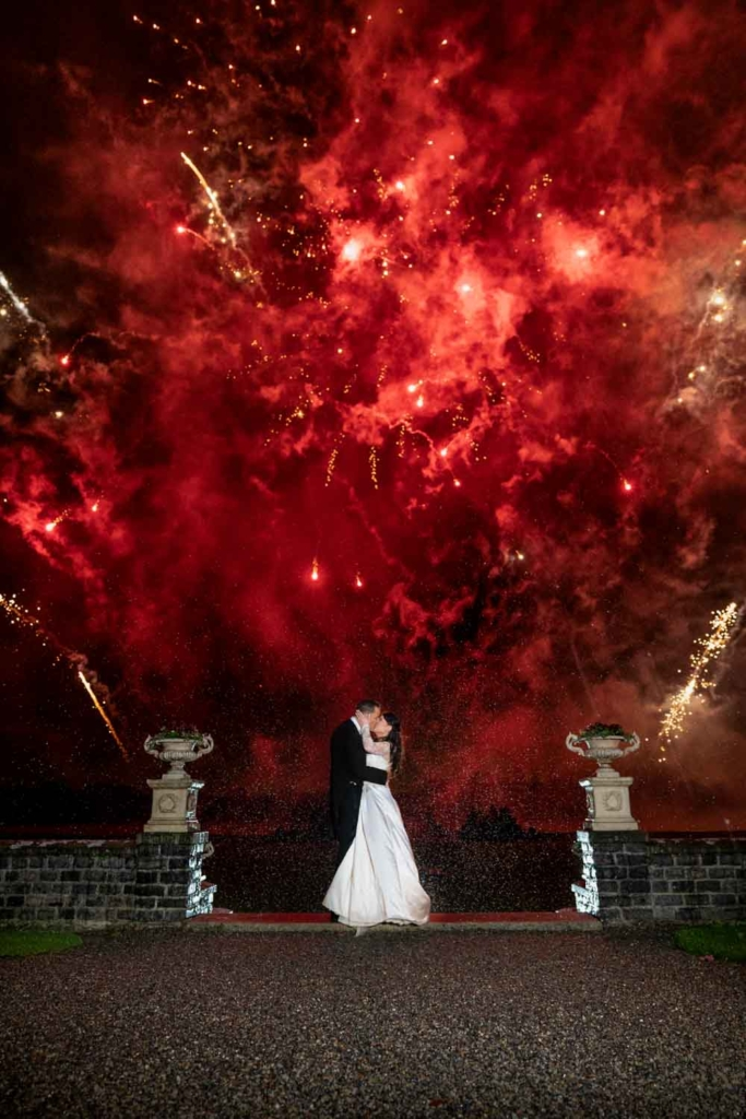 Bride and Groom kissing during the fireworks at their Ireland castle wedding photo by The Fennells